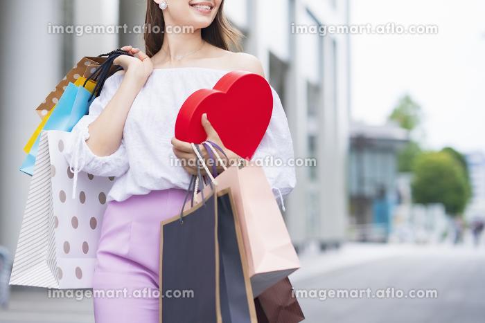 たくさんの買い物袋を抱える女性の販売画像