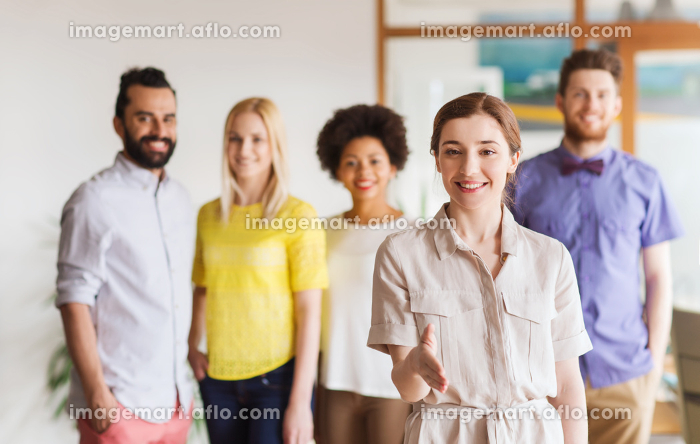 woman making handshake over creative office teamの販売画像