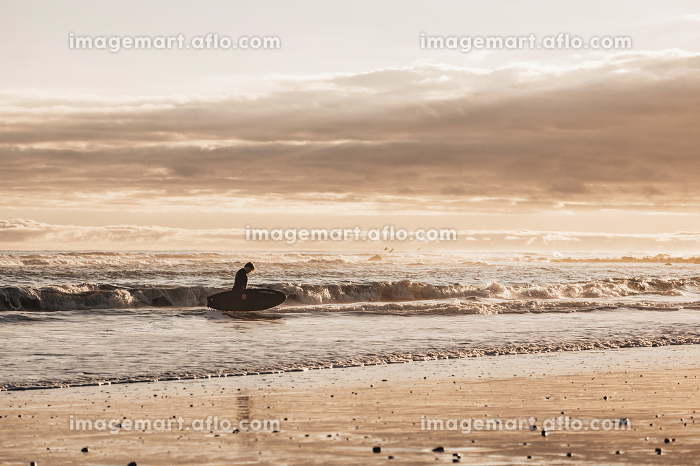 Tween boy with a surfboard in the water during sunsetの販売画像
