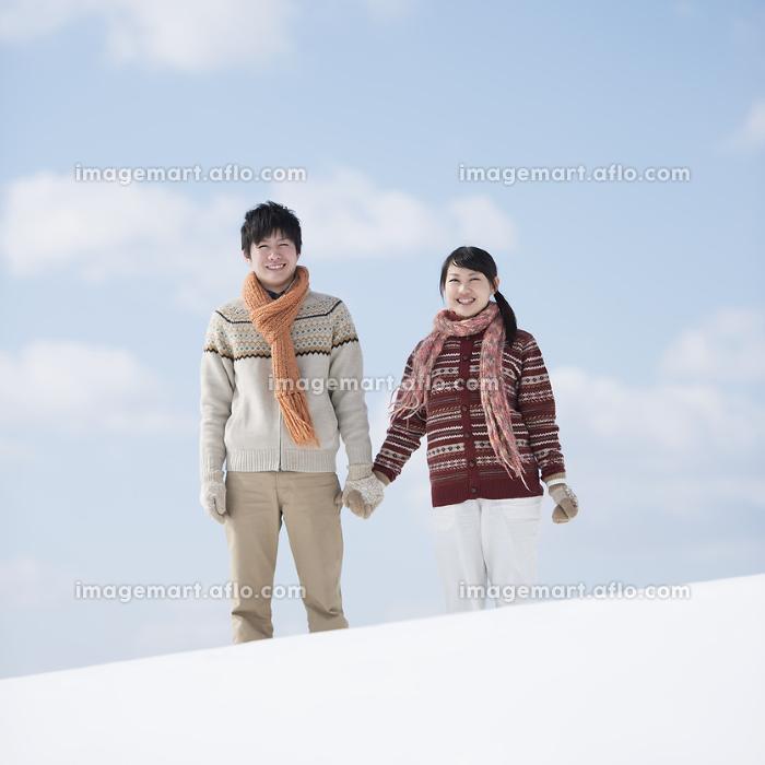 雪原で手をつなぐカップルの販売画像