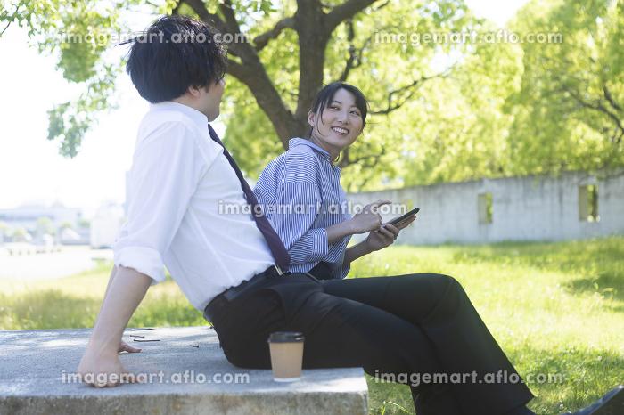 公園で休憩する男女の販売画像