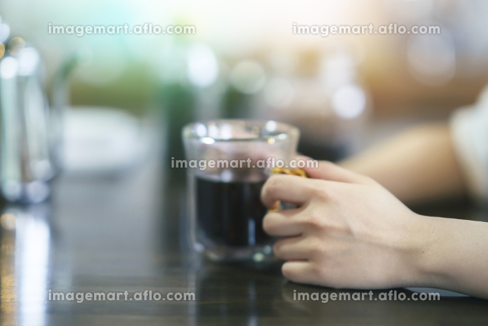 暖かい雰囲気の空間で、コーヒーを飲む若い女性の販売画像