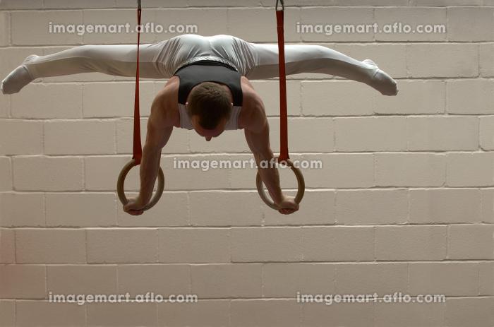 Male gymnast performing on ringsの販売画像