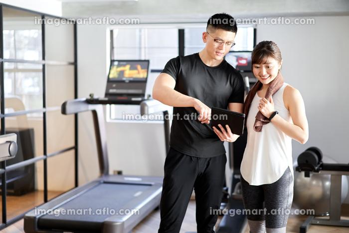 タブレットを使って指導するアジア人男性パーソナルトレーナーの販売画像