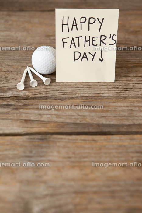 Fathers day greeting card and golf ball on table