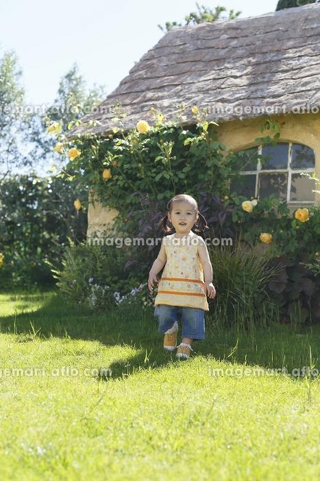 芝生とバラのある庭で遊ぶ女の子