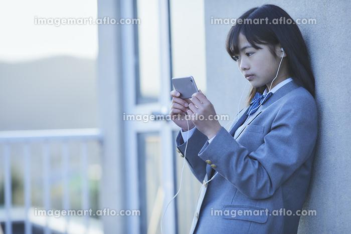 学校の屋上でスマートフォンを見る女子中学生の販売画像