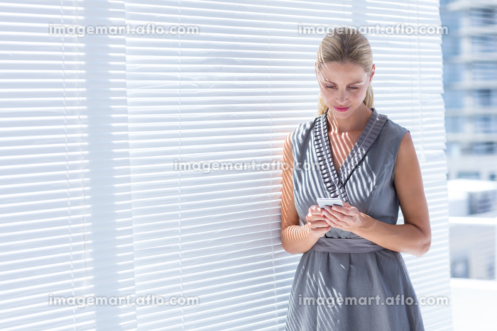 Concentrated businesswoman sending a text messageの販売画像