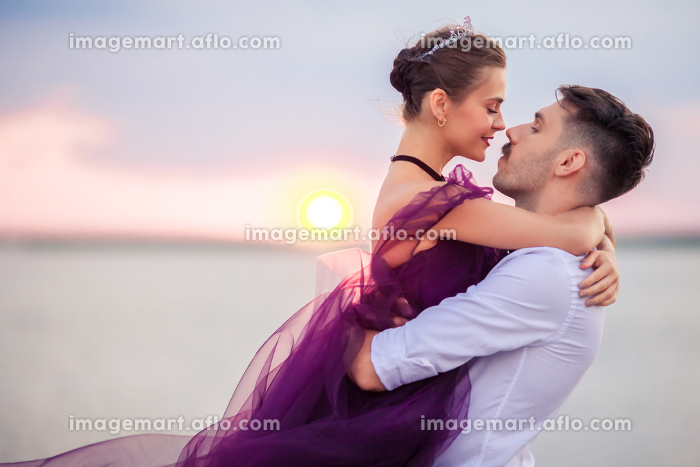 Young romantic couple relaxing on the beach watching the sunsetの販売画像