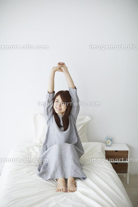ベッドの上で伸びをする日本人女性