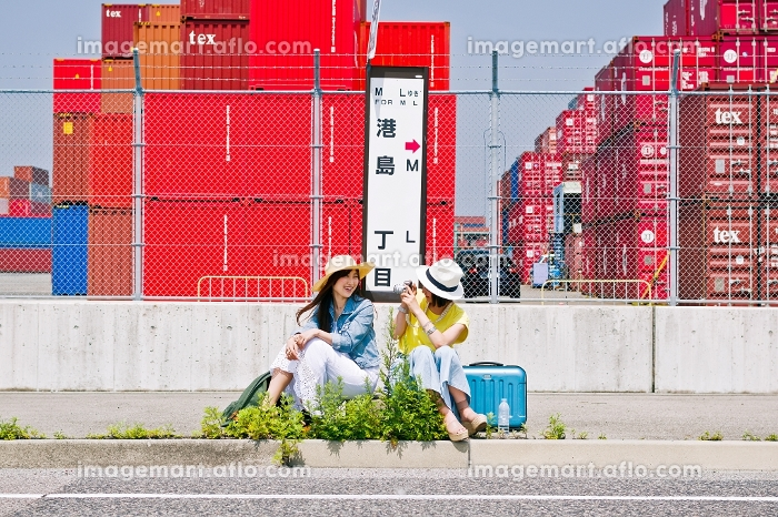 バス停で写真を撮る女性