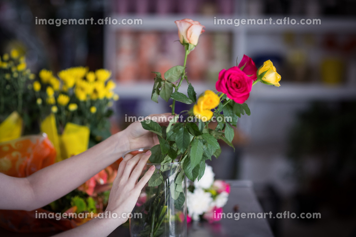 Female florist arranging flower bouquet in vase