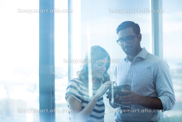 Business couple holding digital camera against glass window in officeの販売画像