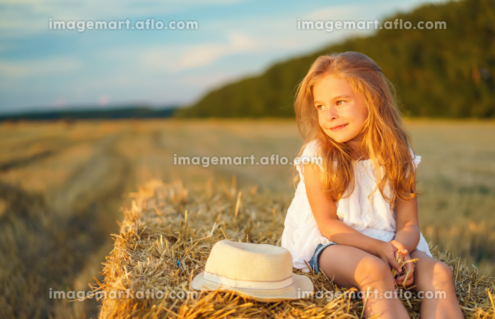 Little girl in a field with hay rollsの販売画像