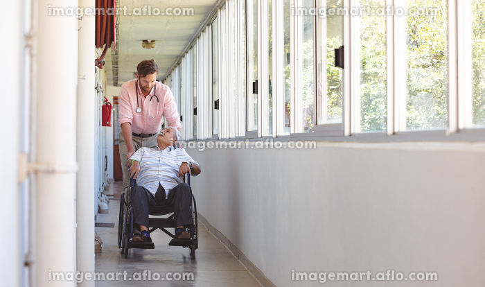 Front view of male Caucasian doctor and senior man talking with each other while Caucasian doctor pushing his wheelchairの販売画像