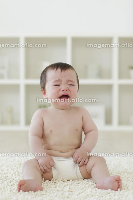 リビングに座って泣いているハーフの赤ちゃんの販売画像
