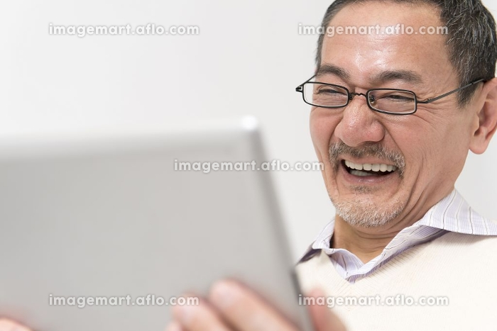 タブレットPCを持って笑うシニア男性