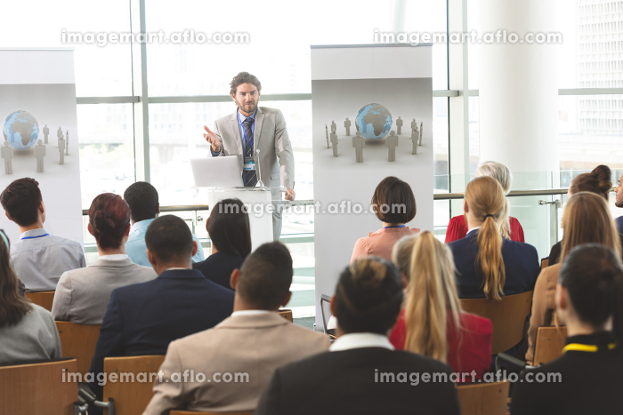 Front view of Caucasian businessman with laptop speaks in front of diverse crowd of business people at business seminar in office buildingの販売画像