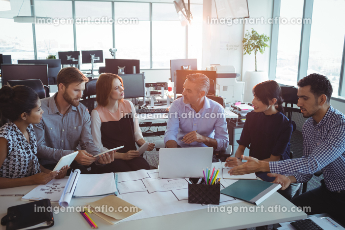 High angle view of creative business colleagues discussing around deskの販売画像