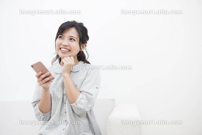 スマホを持つ笑顔の女性