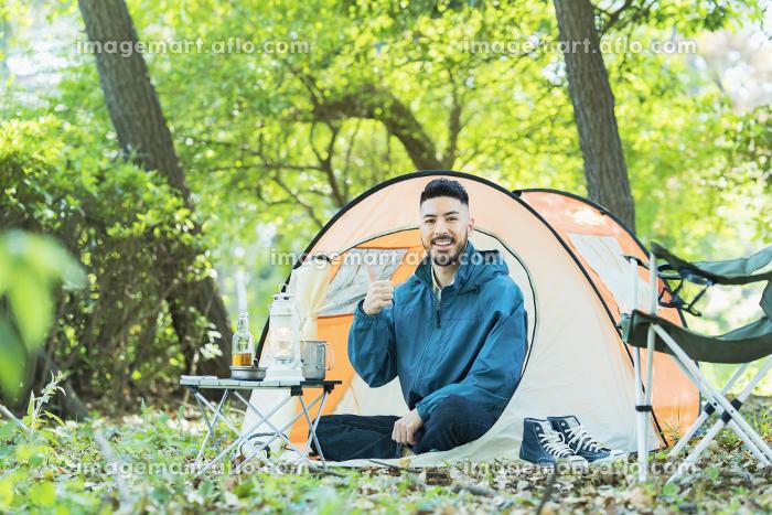 テントの前で笑顔でポーズする男性の販売画像