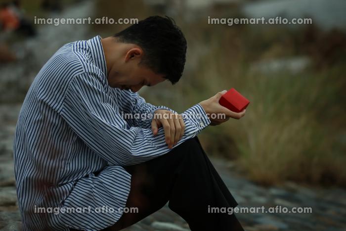 リングケースを手に持ち涙を流す男性の販売画像
