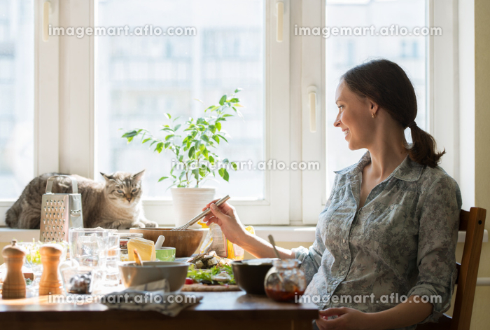 Woman cooking pizza at home. Filling dough with ingredients, while cat relaxing on windowの販売画像