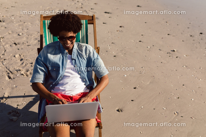 Front view of young African-american man using laptop while relaxing in a beach chair on the beachの販売画像