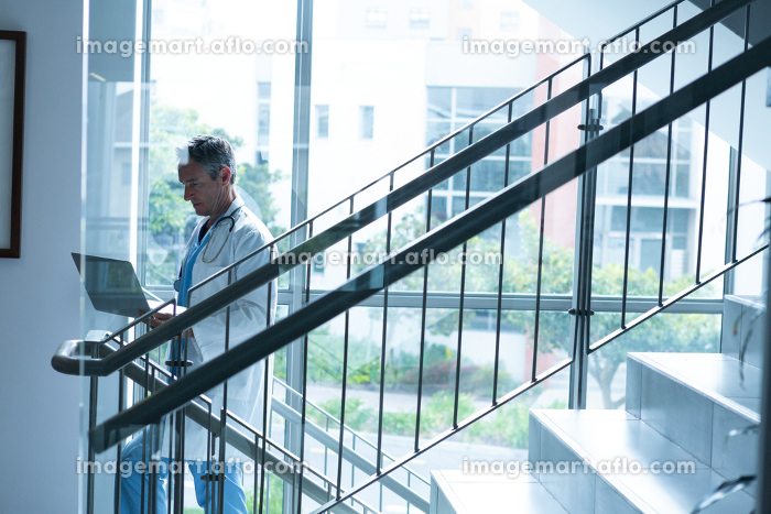 Side view of mature Caucasian male doctor using laptop while walking the stairs in  hospital. Shot in real medical hospital with doctors nurses and surgeons in authentic settingの販売画像