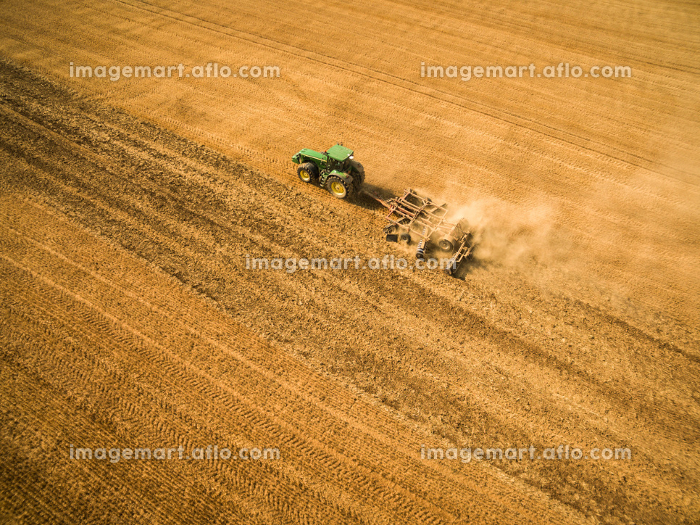 Aerial view of a tractor working a field after harvestの販売画像