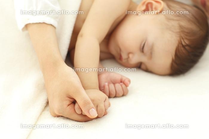 眠る赤ちゃんの手に触れるお母さんの手の販売画像
