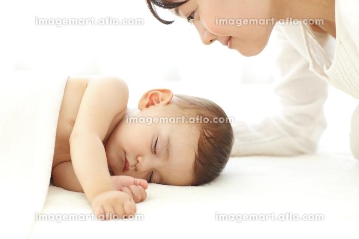 眠る赤ちゃんを見守るお母さん