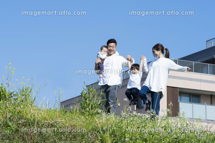 楽しそうにはしゃぎながら散歩する家族の販売画像