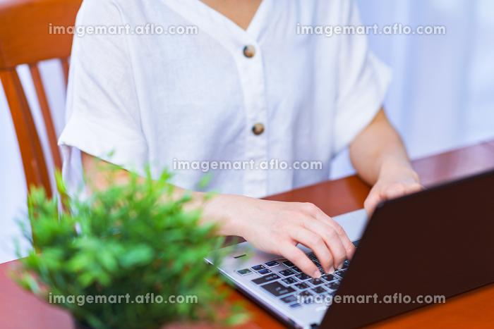レンタルオフィスでリモートワークに励む中年女性【ウィズコロナのニューノーマル】の販売画像