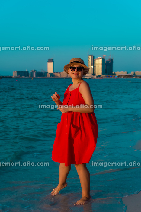 Woman in red dress waking along the beach and enjoing lifeの販売画像