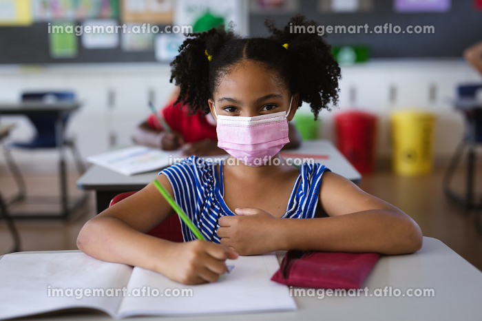 Portrait of african american girl wearing face mask sitting on her desk in the class at school. education back to school health safety during covid19 coronavirus pandemicの販売画像
