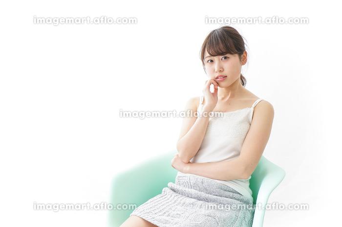 イスに座って喜ぶ女性の販売画像