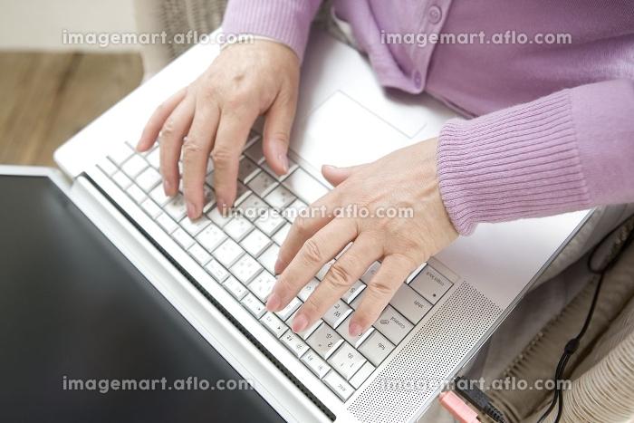 パソコンのキーボードをたたくシニア女性の手元の販売画像
