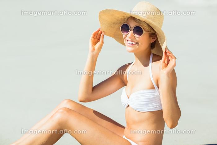 Young woman in bikini posing with hat