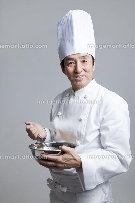 玉子をかき混ぜる調理師の販売画像