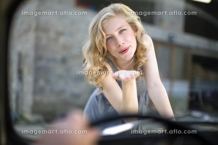 車内の男性に投げキスをする女性の販売画像