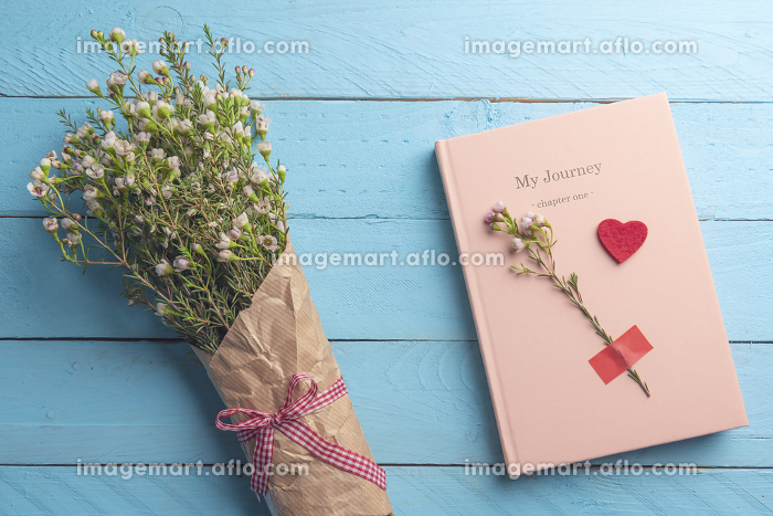 Pink journal and flowers bouquet. Flat lay on blue backgroundの販売画像