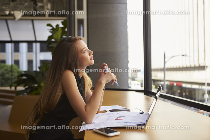 Businesswoman working in an office looking out of the windowの販売画像