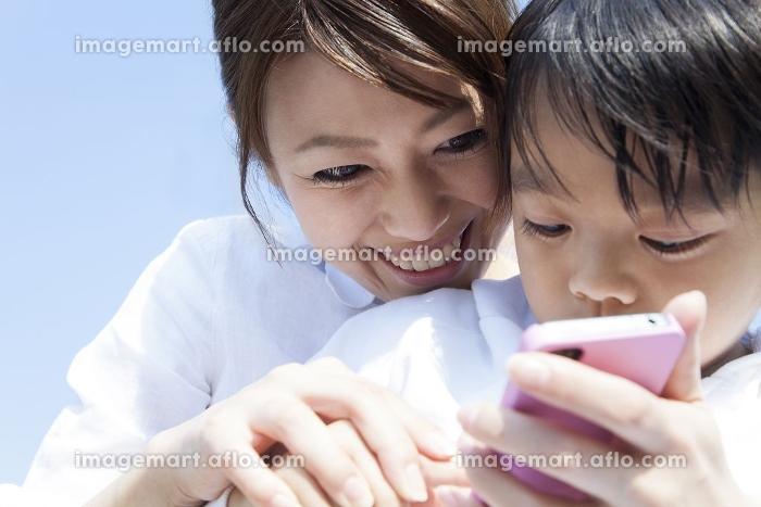 スマートフォンを持つ母子の販売画像