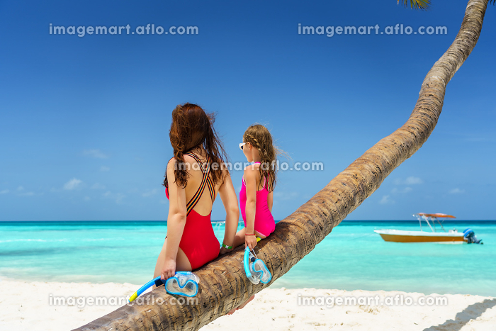 Young mother and little daughter sitting on palm tree on the beach in Dominican Republicの販売画像