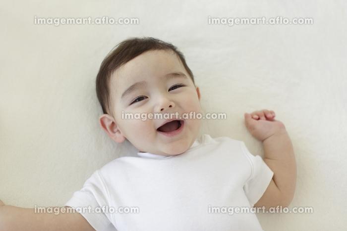 ベッドの上に寝転がる赤ちゃんの販売画像