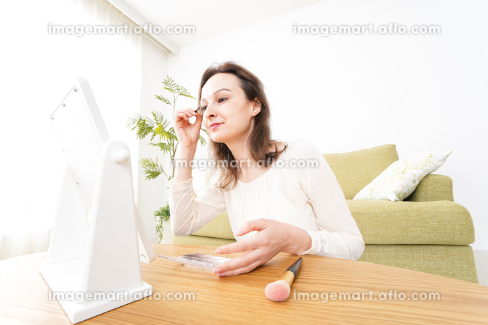 自宅で化粧をする若い女性の販売画像
