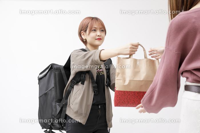 フードデリバリーをしている女性の写真の販売画像
