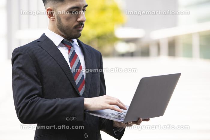 ノートPCを持つビジネスマンの販売画像