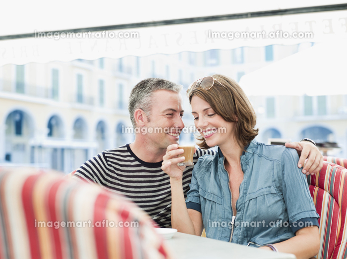 couple sitting in a city cafe laughingの販売画像